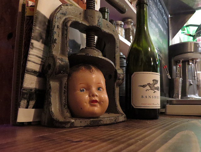 Baby doll head in a vice with a bottle of wine at The Fremont Diner.