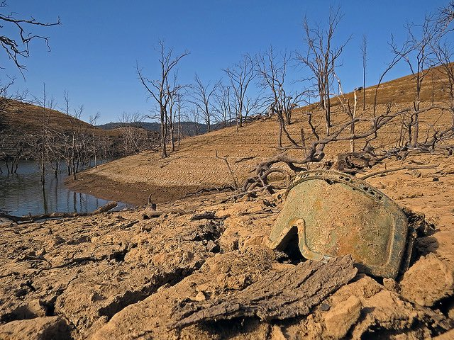 Extreme drought, low water level, ski goggles and cracked earth at New Melones Lake in 2015.